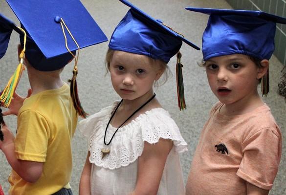 Three prekindergartners with blue mortarboards preparing to graduate and move up to kindergarten