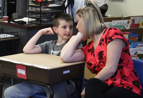 Student and teacher sitting together at a desk and talking
