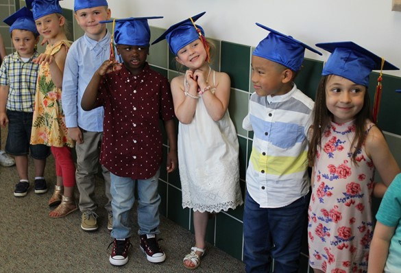 Preschoolers wearing bright blue mortarboards lined up in the hallway in preparation for their graduation ceremony
