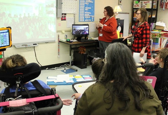 Students discussing a book with a class in a different state via videoconference