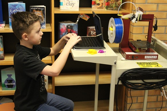 Student in a library makerspace using a digital printer