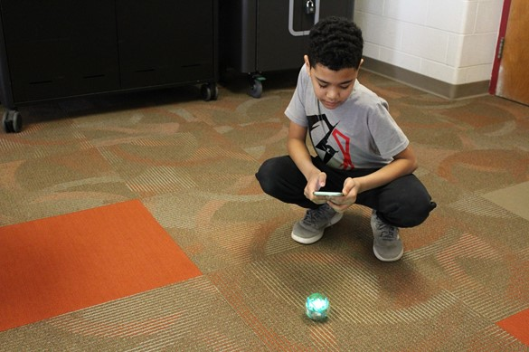 Student programming a small robot in a library makerspace