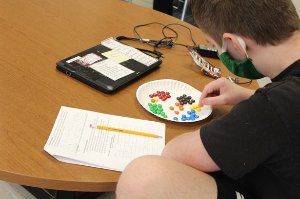 Student working out a math problem using M&Ms candies