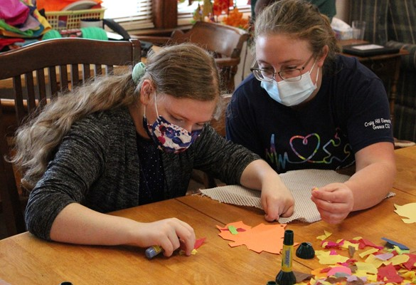 Student and staff member working on crafts at the ADL House