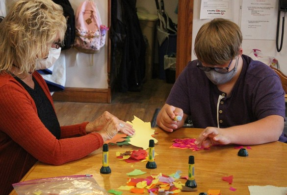 Student and staff member working on crafts