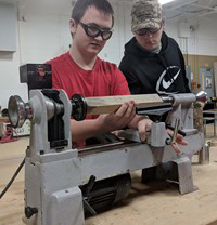 Two students examines a piece of wood on a lathe.