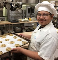 A student in chef's clothing holds a baking tray of cookies