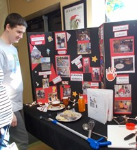 A student looks over a tabletop display of the areas of study in Personal Services