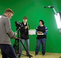 Three students prepare to shoot video in front of large green screen