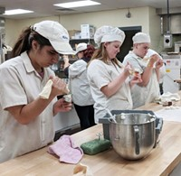 Three students in baking smocks and hats squeeze pastry bags to create frosting roses.