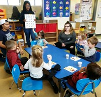 In a colorful classroom, six preschool children sit around a table. One student in the Child and Family Development program holds a chart with alphabet letters while two other high school students look on.