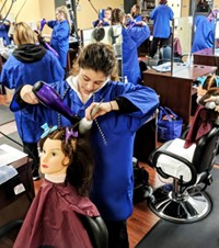A student in a smock uses a blow dryer and brush on a mannequin head that is supported on a salon chair, while several other students also working on mannequins are visible in the classroom background.