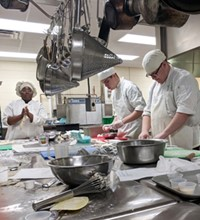 Three students in chef's hats and aprons prepare food at a large steel prep table, with many cooking tools and pots hanging overhead and on the table.