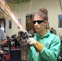 A student in full safety gear uses a hand held power tool that is creating a shower of sparks while sanding metal.