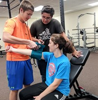A student sitting on exercise equipment has her blood pressure taken by another student, while a third student looks on.