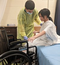 One student wearing protective medical clothing helps another student, who is acting as a patient, transfer from a hospital bed into a wheelchair