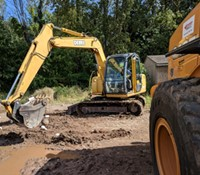 A student operates an excavator, preparing to scoop soil.