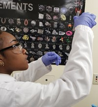 A student in safety goggles and medical protective clothing examines a test tube sample by holding it up to the light.