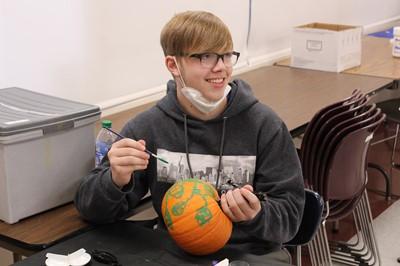 Westside student painting a pumpkin
