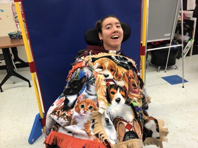 Student displaying blankets featuring dogs and cats