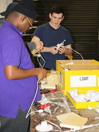 Two students stand at a table adding wires to light fixture bases