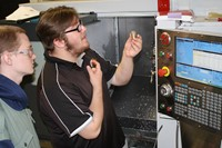 A student examines a metal part while another looks on, with a CNC lathe behind them.