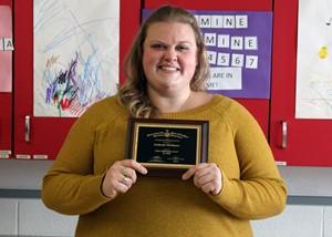 Katie McElhaney holding award