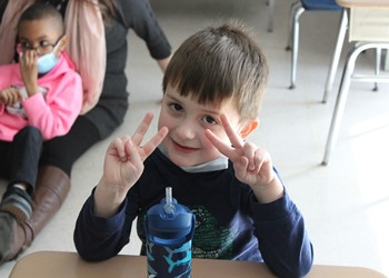 """Smiling student flashing """"Victory"""" signs with his fingers"""