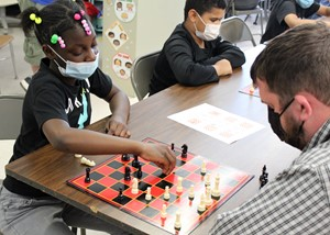 Student playing chess with a staff member