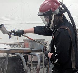 A student wearing a respirator helmet uses a professional sprayer to paint a metal panel.