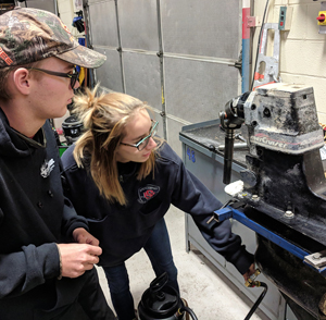 In a classroom a student wearing safety glasses make an adjustment to a hose that is attached to a boat motor.