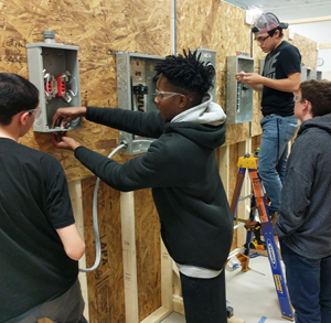 Four students work in an electricity classroom, working in pairs to wire junction boxes mounted to a wall.